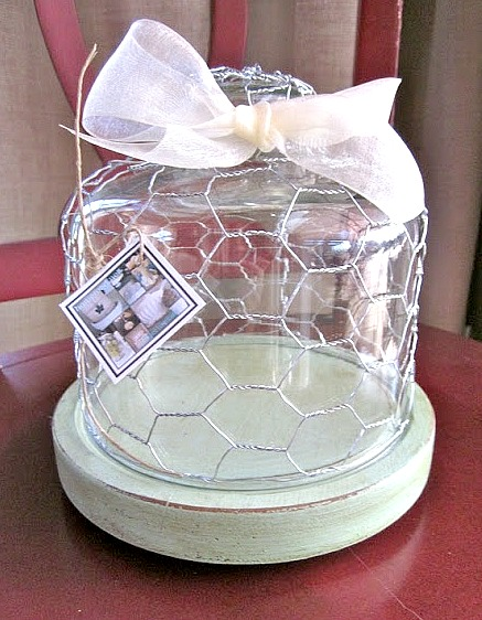 Glass cloche with bow and chicken wire on green dish