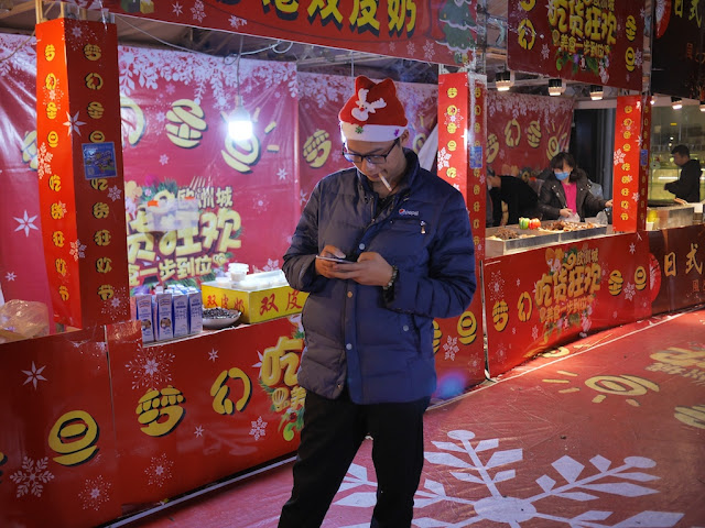 man wearing Santa cap smoking and looking at a mobile phone