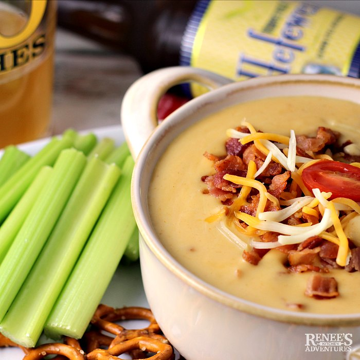 Beer Cheese Dip with Bacon on platter with celery and pretzels, beer in glass and in bottle