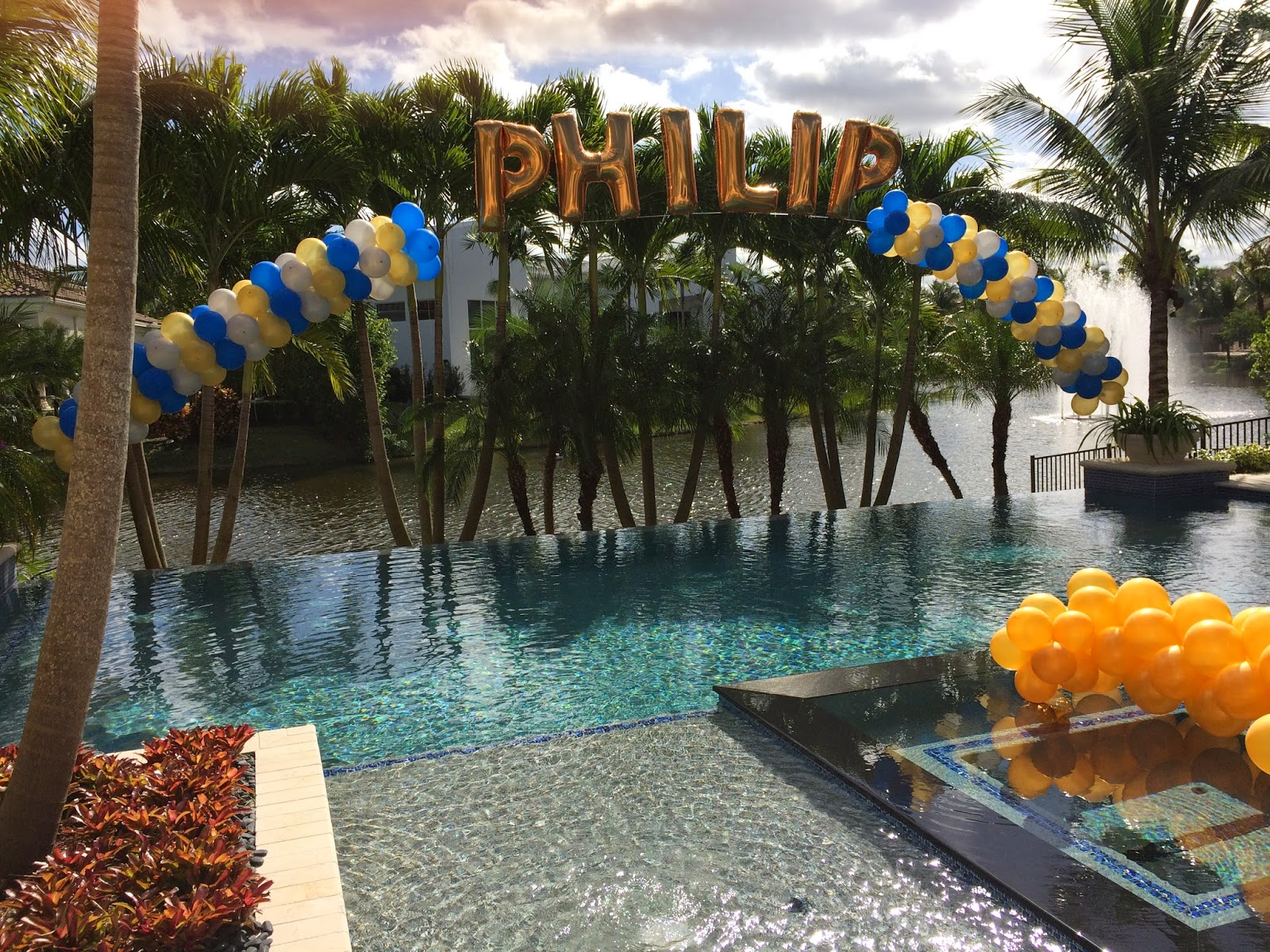 Balloon arch with name over swimming pool