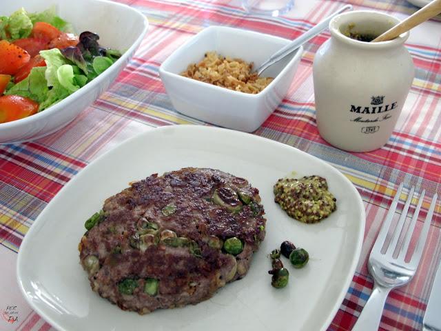 Hamburguesa de ternera aderezada con guisantes, habitas tiernas y cebolla frita.