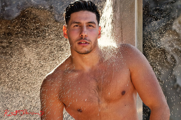 Mid to head-shot, back-lit water spray. Outdoor harbour beach location with shower spray. Male modelling portfolio shot on Location in Sydney Australia by Kent Johnson.