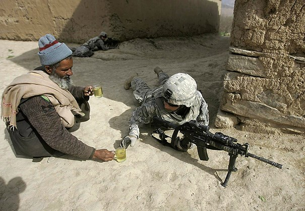 An Afghan man offers tea to thirsty fighting American soldiers.