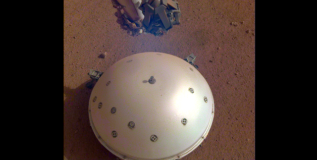 This image, taken March 19, 2019 by a camera on NASA's Mars InSight lander, shows the rover's domed Wind and Thermal Shield, which covers its seismometer, the Seismic Experiment for Interior Structure, and the Martian surface in the background. Credits: NASA/JPL-Caltech