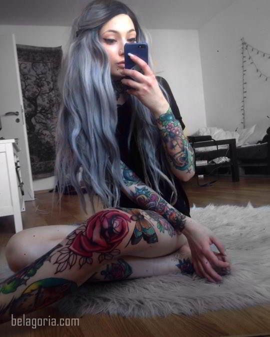 Modelo sentada en la cama, lleva tatuaje de rosa en la rodilla