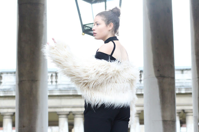 An image of Eboni posing in an Apricot Clothing long haired jacket, black Primark trousers and River Island top