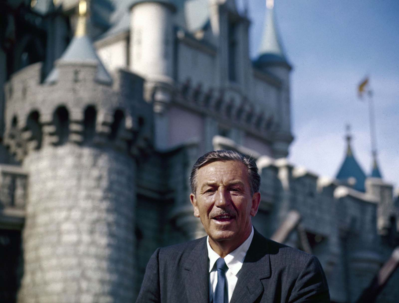 The movie producer and animator Walt Disney smiles as he stands in front of Sleeping Beauty's Castle at the grand opening of Disneyland in 1955.