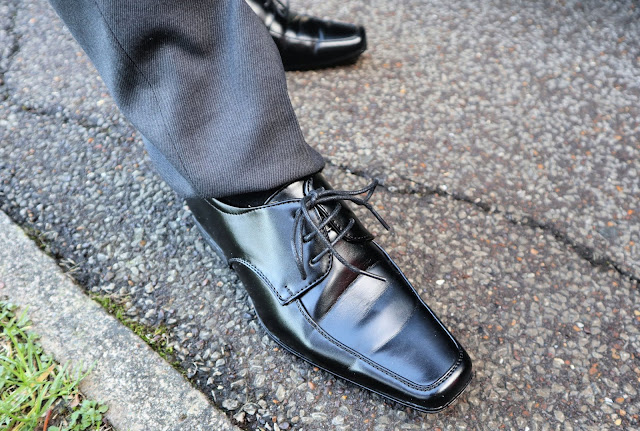 A close up of boys black shoes.