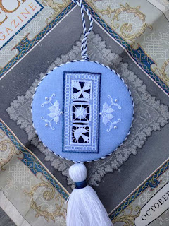Blue fabric ornament embroidered in white with cutout areas filled with three different thread filling stitches