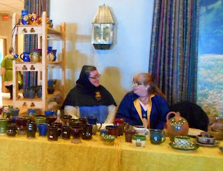 2 women merchants behind their handmade pottery items