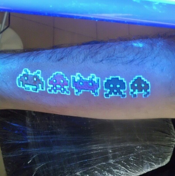 #29. Space invaders. - 30 Glow-In-The-Dark Tattoos That'll Make You Turn Out The Lights.