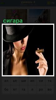 Женщина в шляпе держит в руках сигару, пытаясь курить