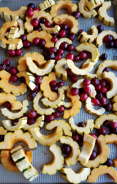 whole cranberries and slices of squash on baking sheet
