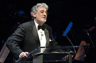 El tenor Plácido Domingo con smoking dirigiendo una orquesta en 2008
