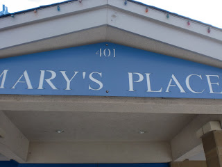 Light blue sign with carved white letters reading MARY'S PLACE