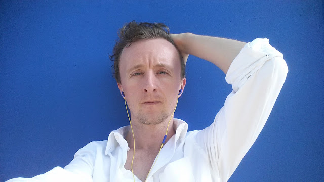 Actor Paul Cram wearing white shirt against blue background