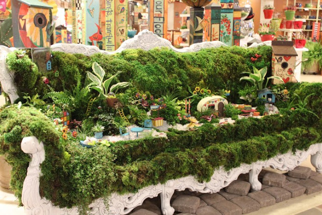 miniature garden display on vintage sofa