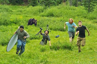 Equipo de fotógrafos corriendo perseguidos por un oso.
