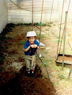 A young boy in a blue shirt and white hat digging with a shovel in a garden.