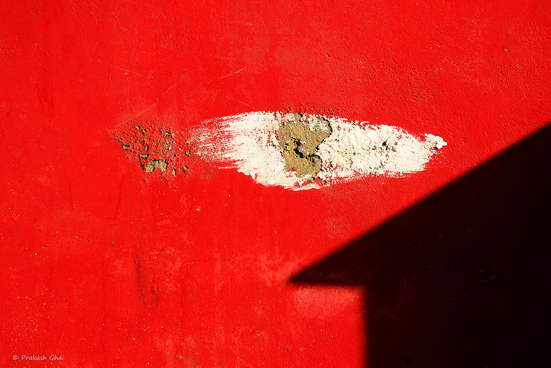 A minimalist photo of White scratch and shadow of a Hut shaped home on a red wall.