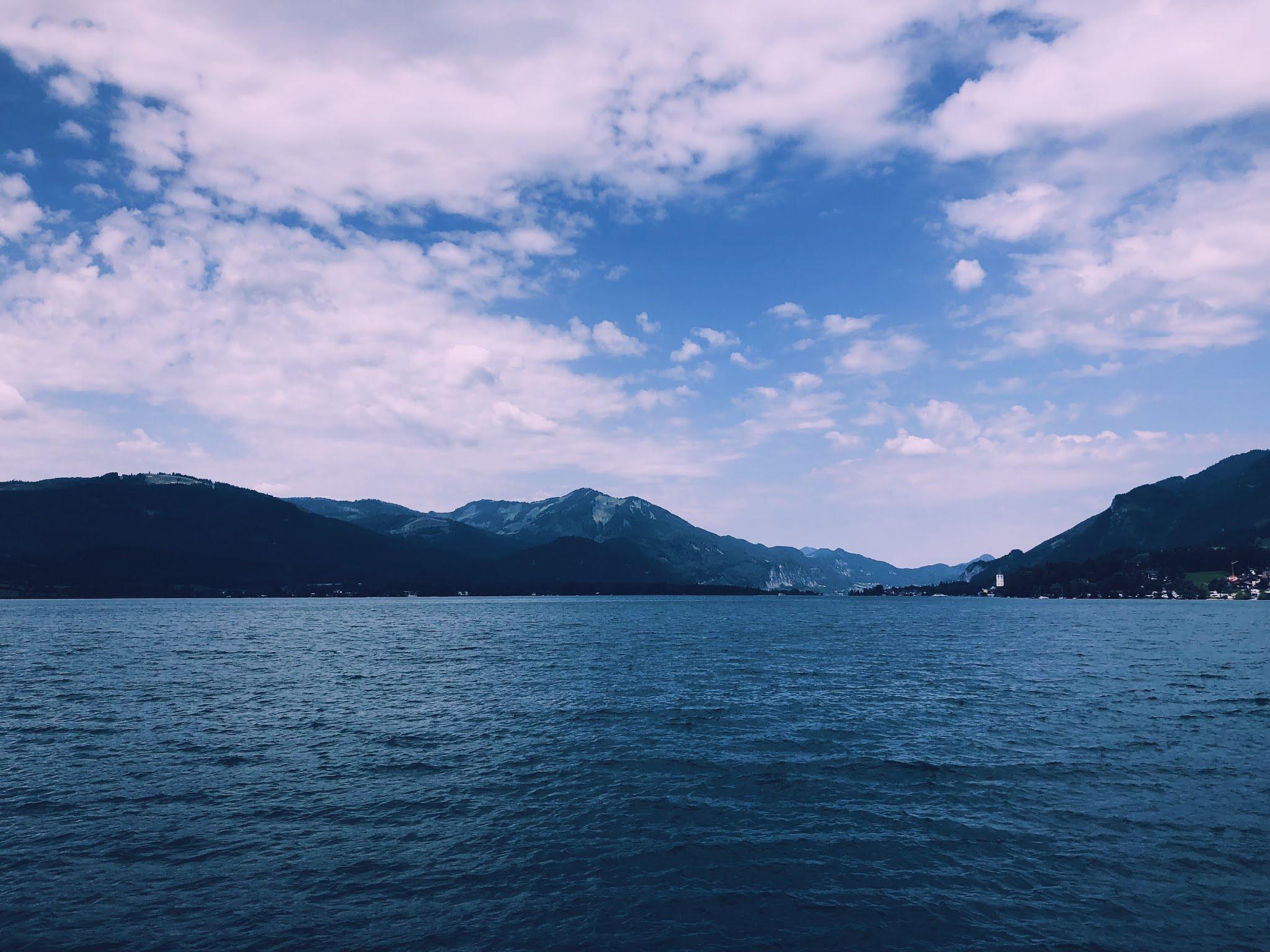 Bergen landschap met wolkenhemel en helderblauw water.