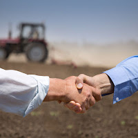 Two people shaking hands in farm field.