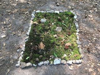 Ein verziertes Steinquadrat am Wegesrand