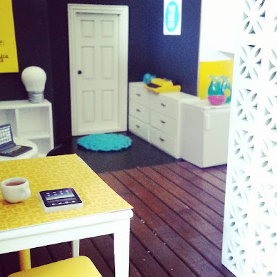 One-twelfth scale modern miniature co-working space with tables, chairs, storage drawers and a divider made of breeze blocks.