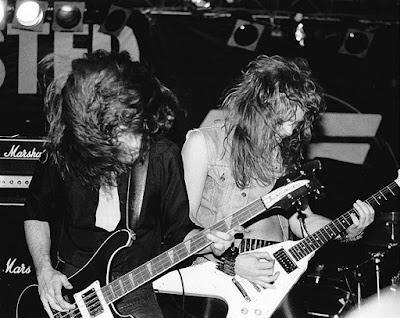 Metallica's Cliff Burton & James Hetfield on stage kicking ass at the Fountain Casino in New Jersey opening up for Twisted Sister December 1983. You can see part of the Twisted banner and logo behind them. Such a fucking incredible photo right!?