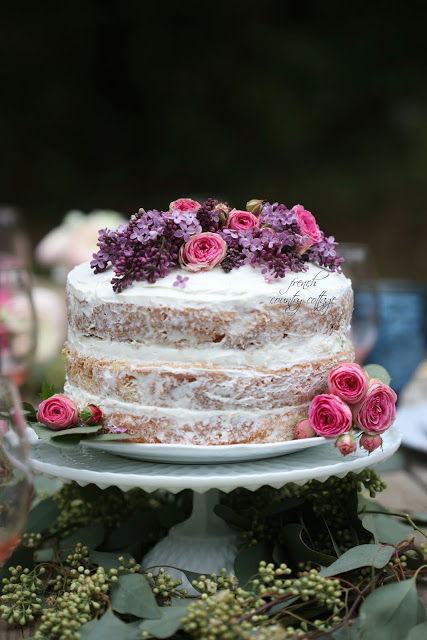 Rustic naked cake topped with lilac and rose flowers