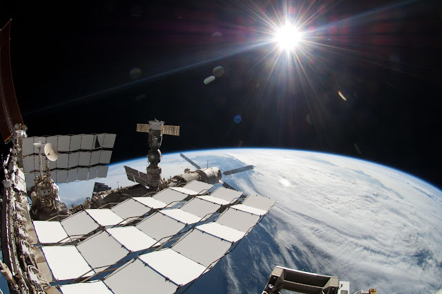 The bright Sun, a portion of the International Space Station and Earth's horizon are featured in this image photographed during the STS-134 mission's fourth spacewalk in May 2011. The image was taken using a fish-eye lens attached to an electronic still camera.   Image Credit: NASA Explanation from: http://www.nasa.gov/multimedia/imagegallery/image_feature_2059.html
