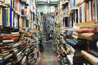 A pathway between stacks of books in front of bookshelves full of books.