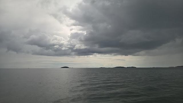 Pilvinen taivas ja tyyni meri.