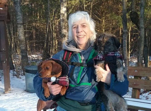 hiker holding small dogs