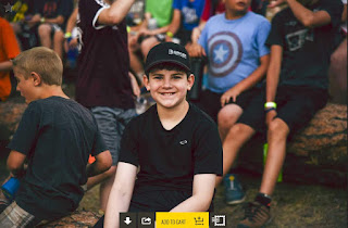 boy in black t-shirt and black hat smiles for camera while random kids mill around in background