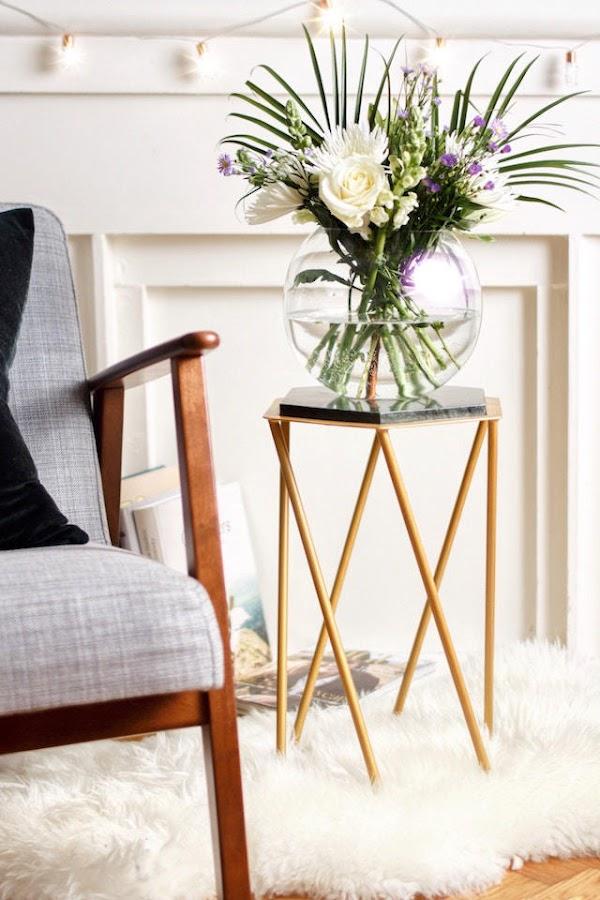Mesita auxiliar con patas en color dorado y sobre de mármol negro, con jarrón y flores
