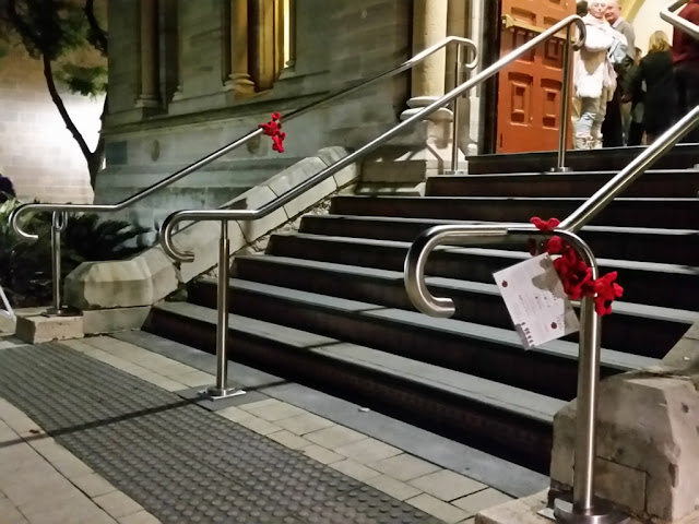 The stairs at the front entrance of the Elder Conservatorium. there are chrome bannisters on each side and one in the centre. The outside bannisters have strings of poppies attached. The nearest poppies also have a leaflet attached.