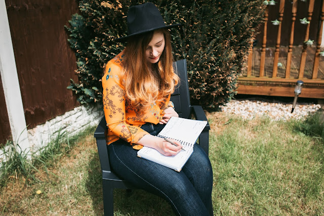 woman sitting outside and writing in journal