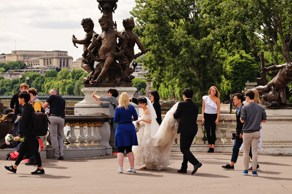 Cherub sculpture, selfies and wedding photography taking place on Pont Alexandre III. Paris photos by Kent Johnson for Street Fashion Sydney.