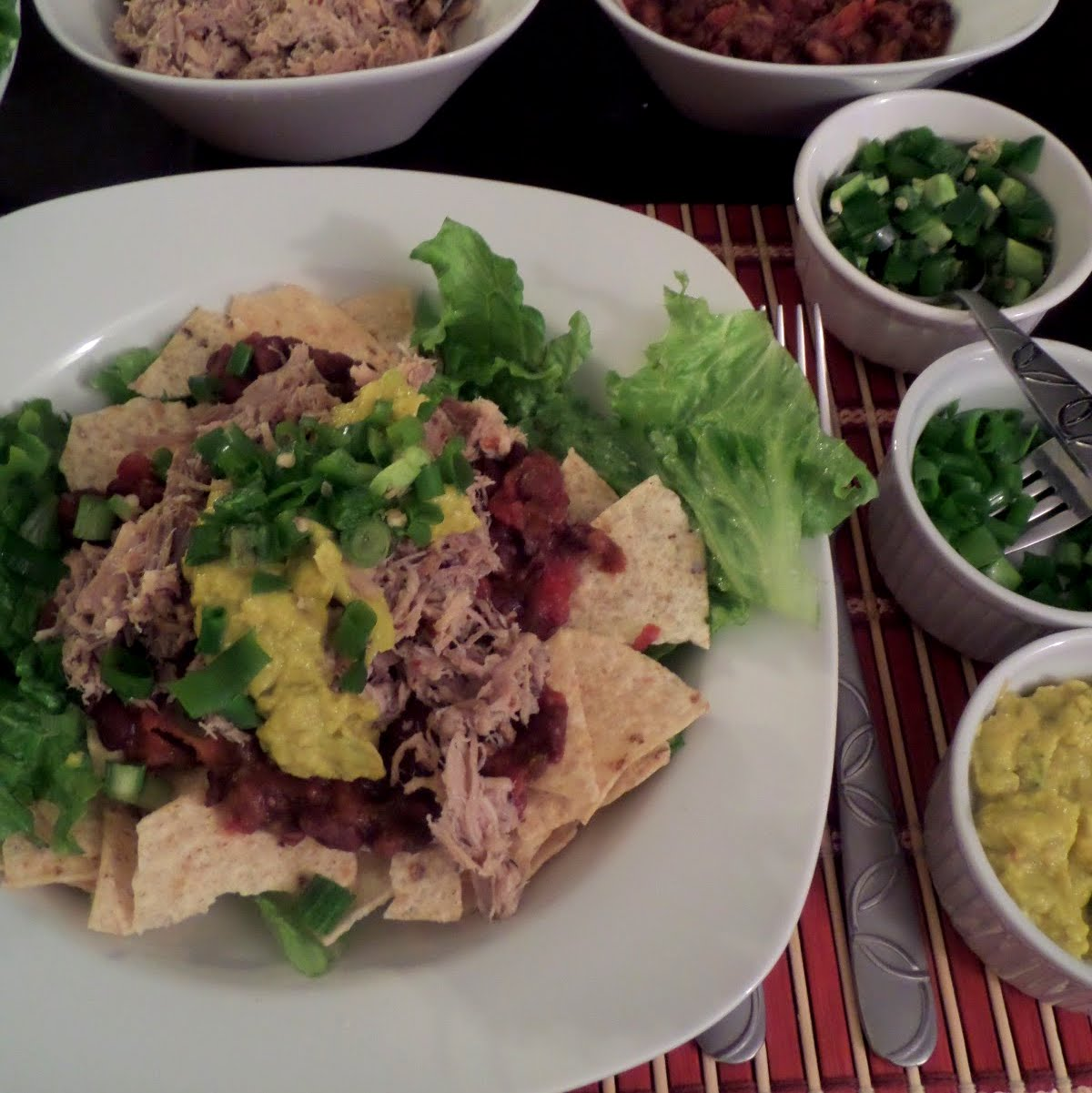 Pulled Pork Taco Salad:  A taco salad topped with spicy black beans, pulled pork, and avocado.