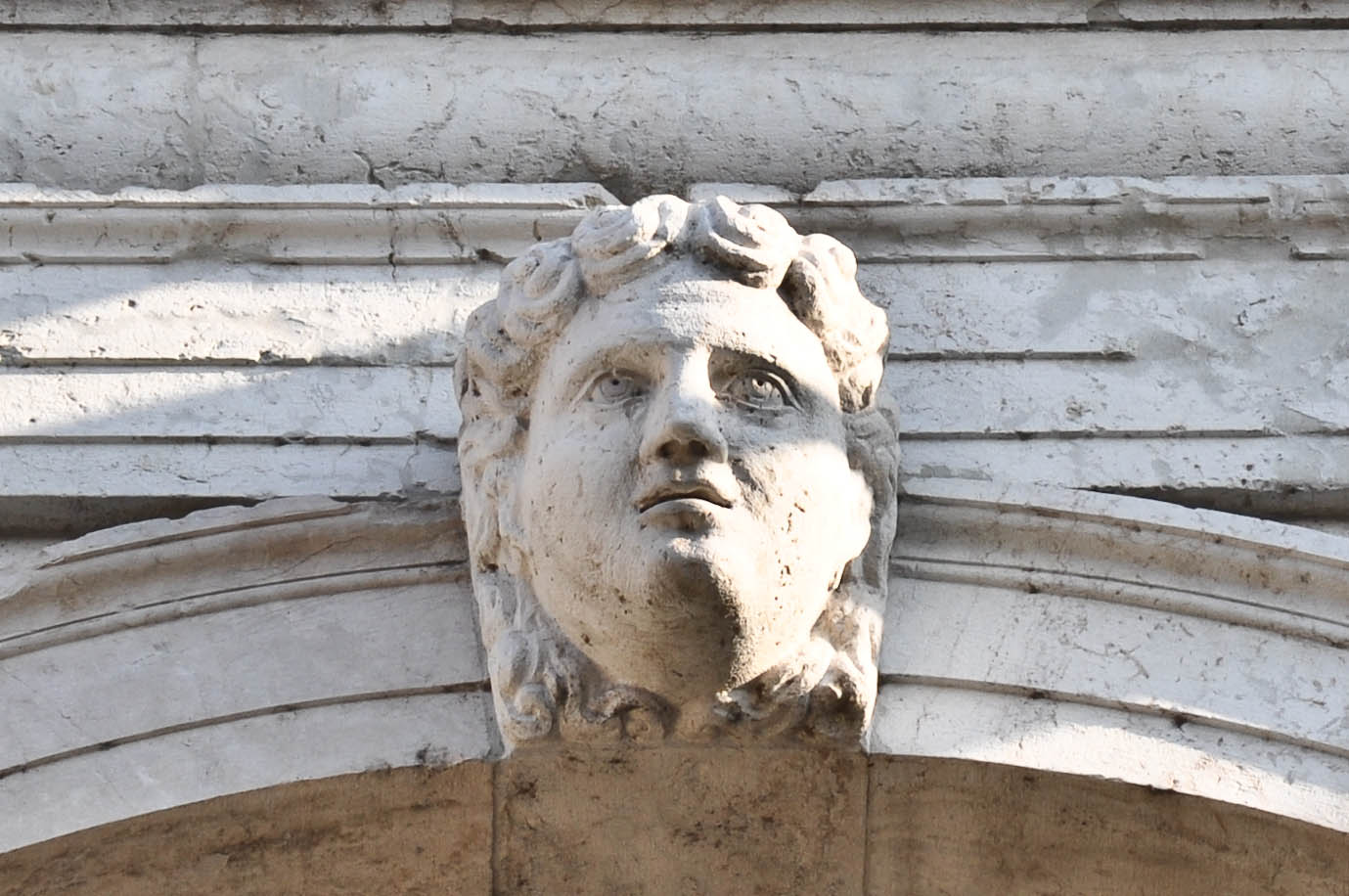 Female face adorning the facade of Palladio's Basilica in Vicenza, Veneto, Italy