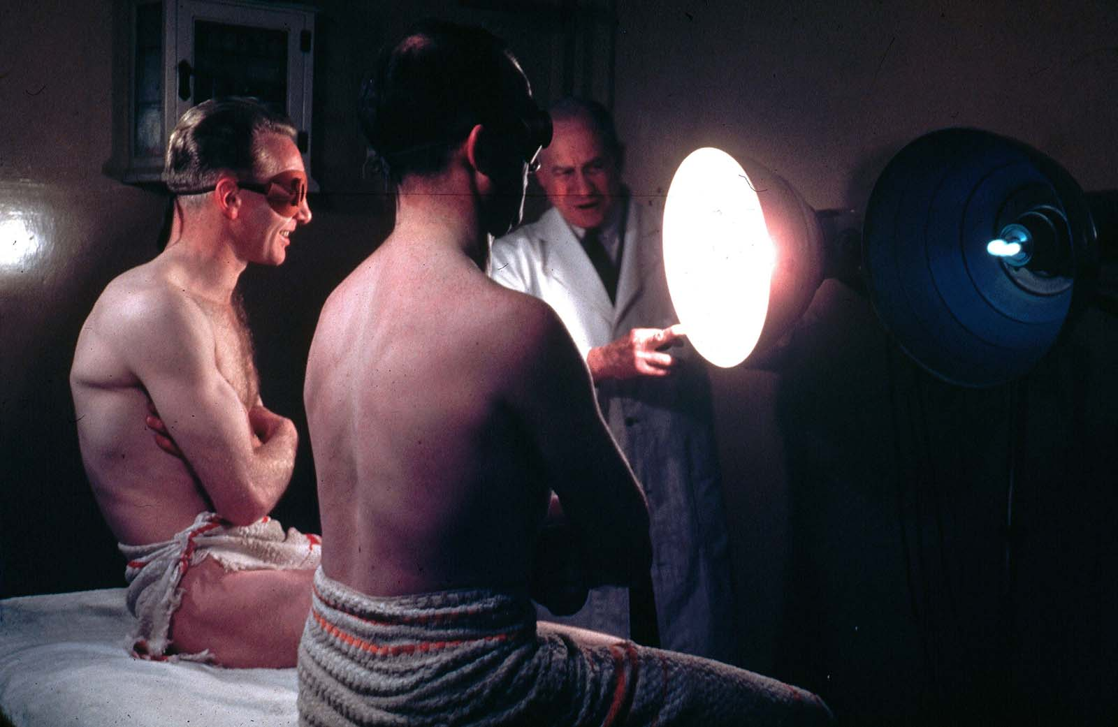 Two men wearing protective eye goggles and towels sitting under sunlamps set up by a doctor. 1950.