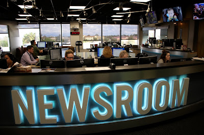 wide shot of newsroom with other reporters working at desks.