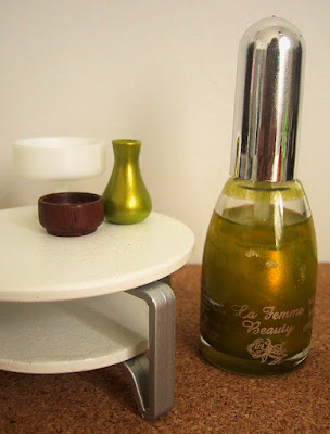 Modern dolls' house miniature coffee table displaying a green vase and two bowls. On the floor next to it is a bottle of nail varnish.