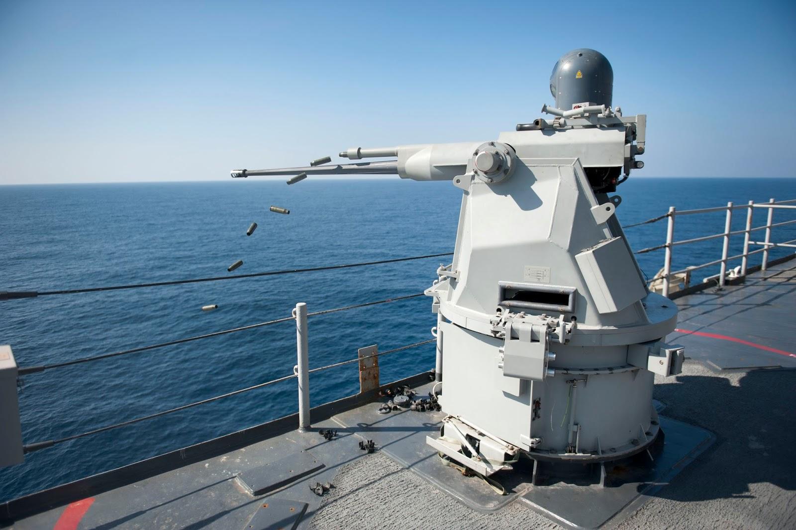 US_Navy_111231-N-KS651-967_A_Mk_38_MOD_2_25mm_machine_gun_system_aboard_the_amphibious_dock_landing_ship_USS_Pearl_Harbor_%2528LSD_52%2529_ejects_casings_d.jpg