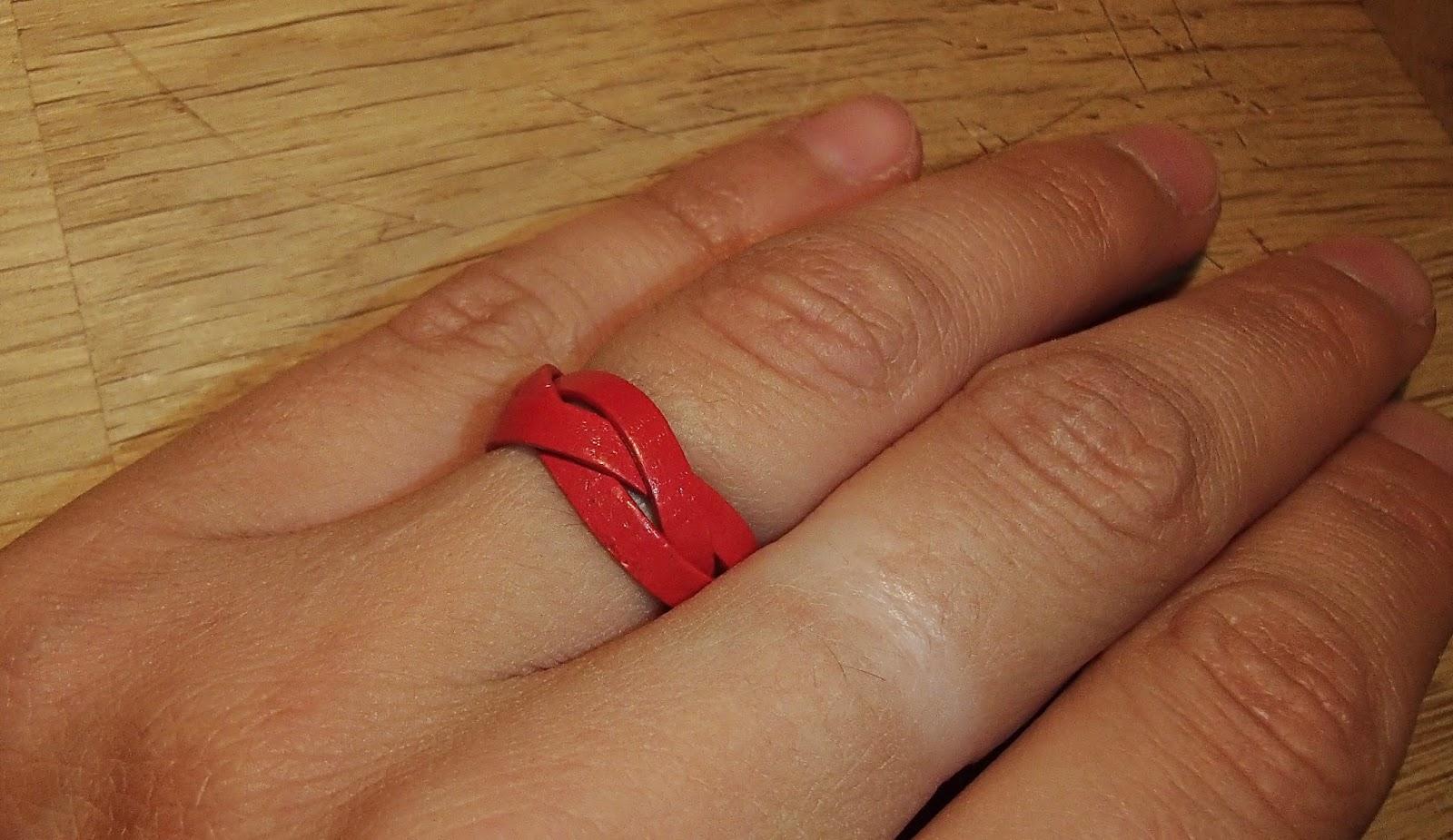 Vue sur une main de la bague rouge en cuir plat tressée