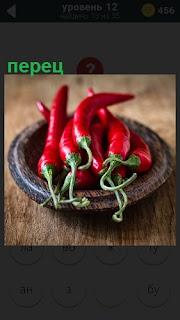 На столе в тарелке лежит несколько стручков красный перец