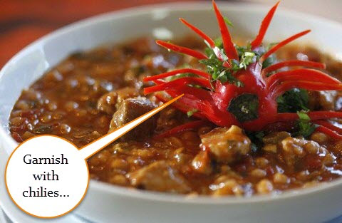 Curry garnished with whole red chili