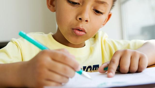 Menino escrevendo com lápis no papel.