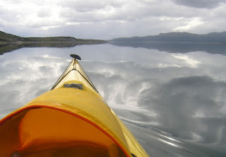 Image from On Polar Tides, Nigel Foster, shows kayak cruising above clouds